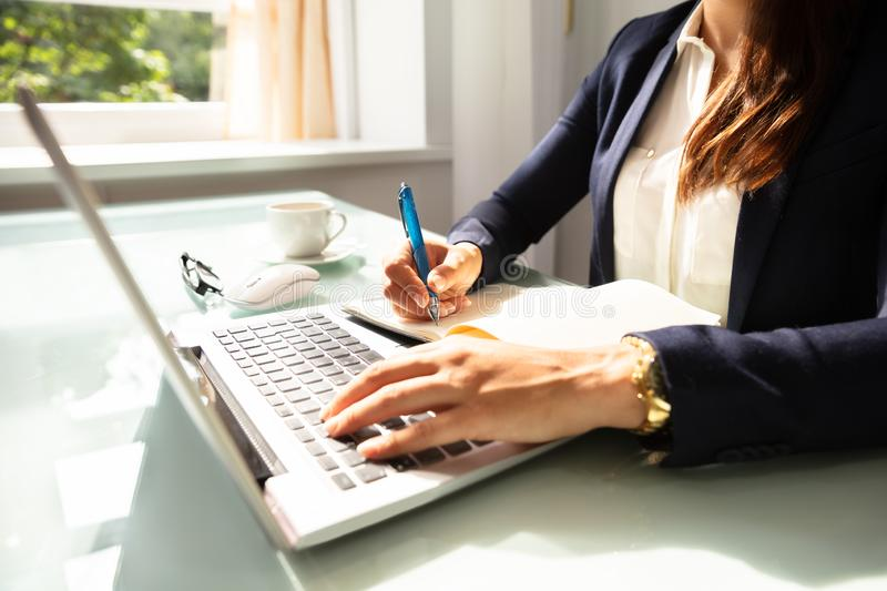 Close-up Of A Businesswoman`s Hand Writing Note In Diary royalty free stock images