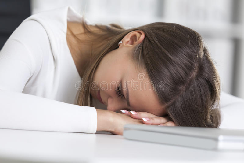 Close up of businesswoman sleeping at work stock image
