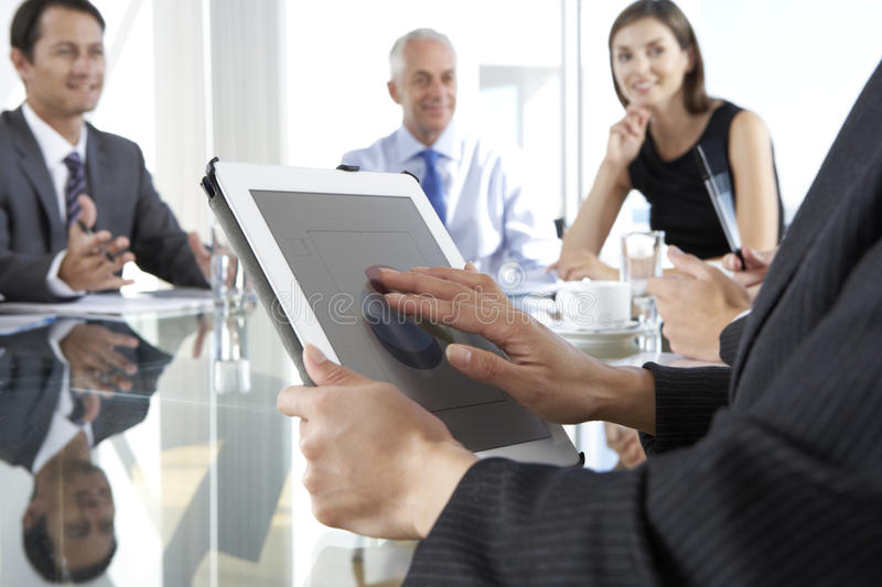 Close Up Of Businesswoman Using Tablet Computer During Board Meeting Around Glass Table stock image