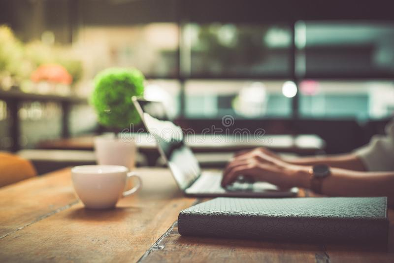 Close up of businesswoman working at office with laptop. Mobile phone and Marketing summary report graph data documents on desk. royalty free stock photos