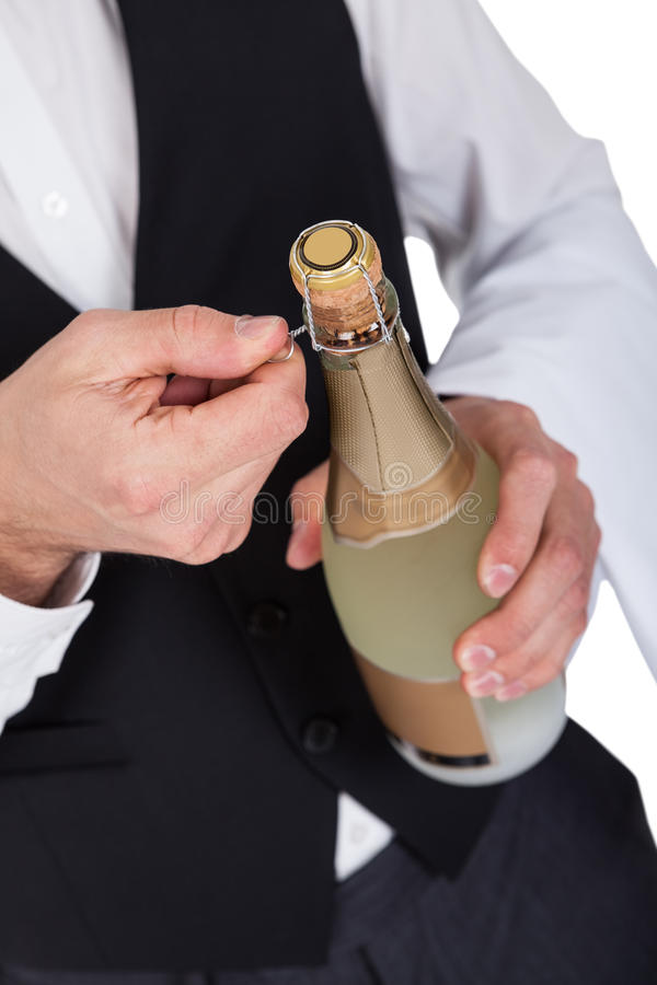 Close-up of butler opening bottle royalty free stock photography