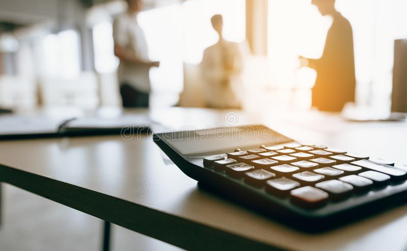 Close up of calculator on desk with business people talking back royalty free stock photos