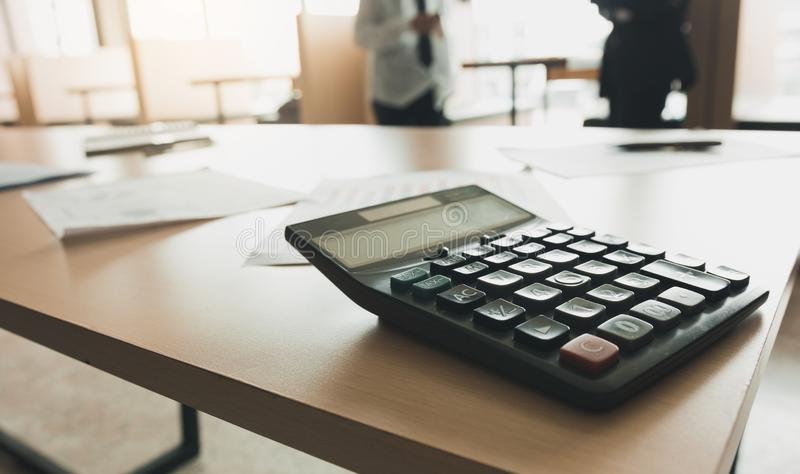 Close up of calculator on desk with business people talking background royalty free stock photography