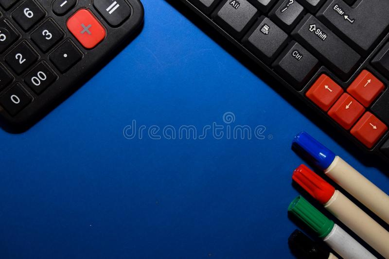 Close up calculator and Keyboard on blue table background stock images