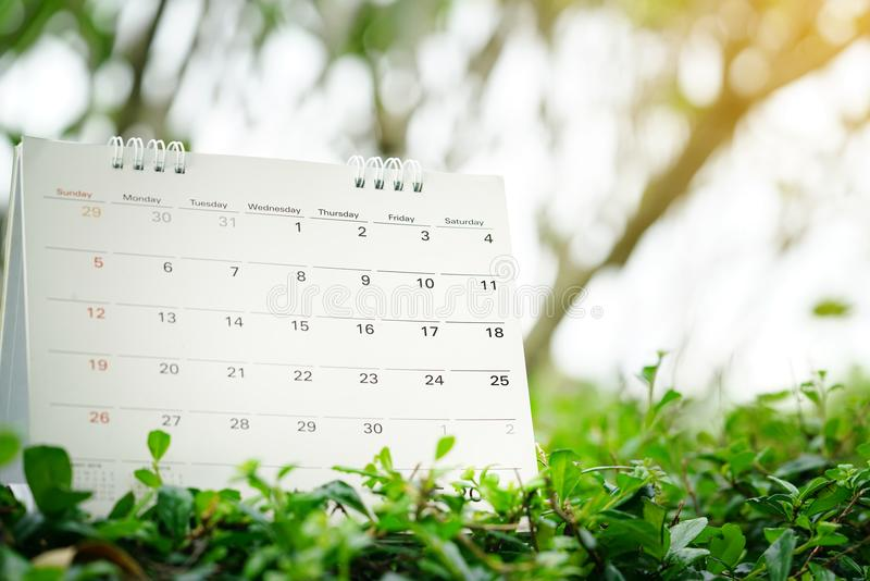 Close up of calendar on green nature background with copy space. Planning for business meeting or travel planning concept royalty free stock photography