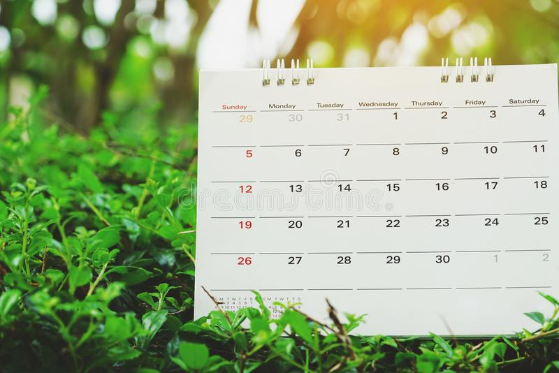 Close up of calendar on green nature background. Planning for business meeting or travel planning concept royalty free stock image