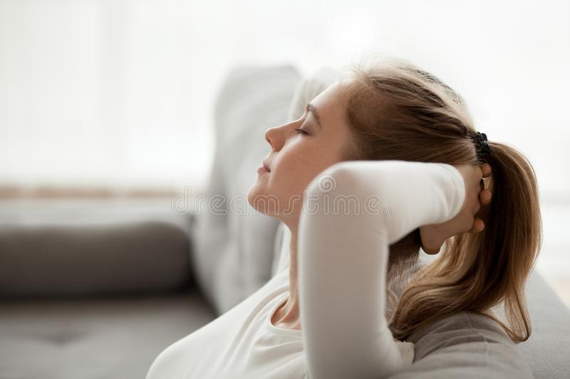 Calm young female relax on couch at home royalty free stock photos