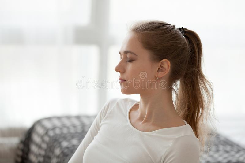 Calm girl with eyes closed meditating at home royalty free stock photos