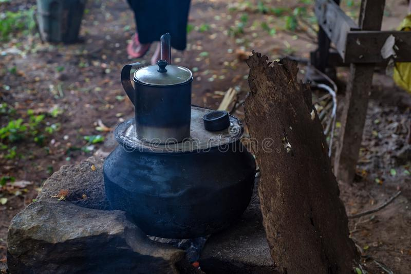 Close up camping fire with pot and metal mug. Closeup image of a dark pot and mug on open fire outdoors camping concept stock images