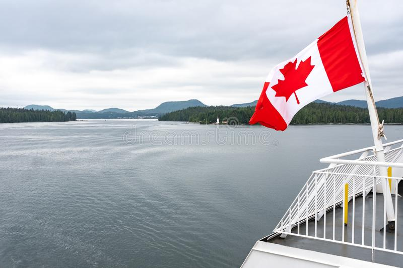 A close up of the Canadian flag flying in the wind at the back of ferry as the boat makes it way through the Inside Passage,. British Columbia, Canada, nobody royalty free stock images