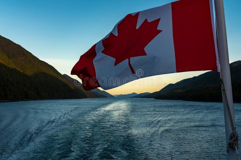 A close up of the Canadian flag flying in the wind at the back of ferry as the boat makes it way through the Inside. Passage with the wake, portrait aspect stock images