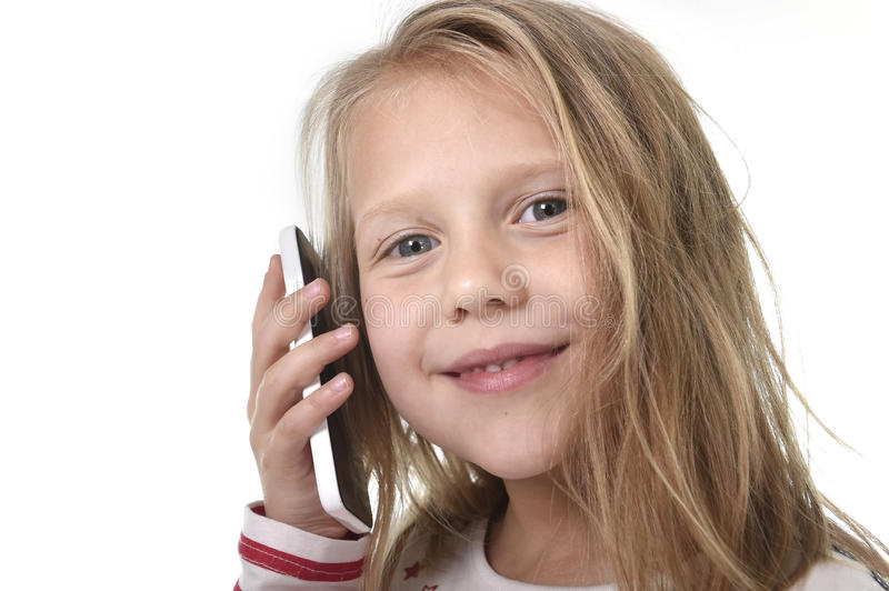 Close up candid portrait of beautiful female child with blond hair and blue eyes using mobile phone talking happy stock photo
