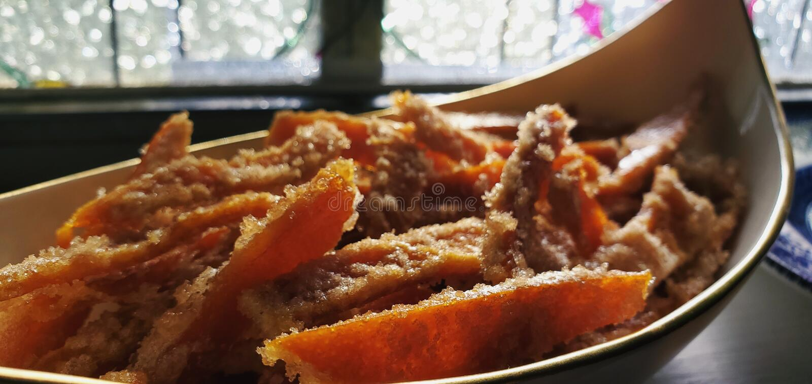 Close up of candied orange peels in candy dish with stained glass window in background stock photography