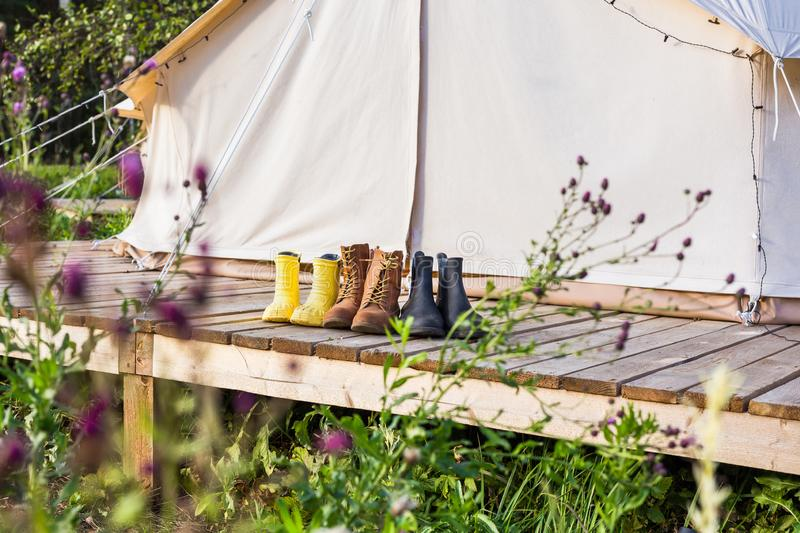 Close-up of a canvas bell tent with shoes on a wooden base stock image
