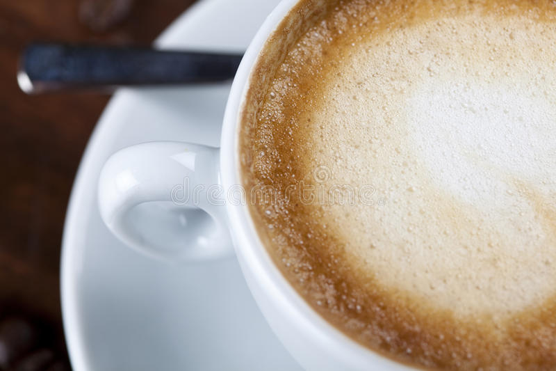 Close-up of a cappuccino coffee cup with milk foam royalty free stock photography