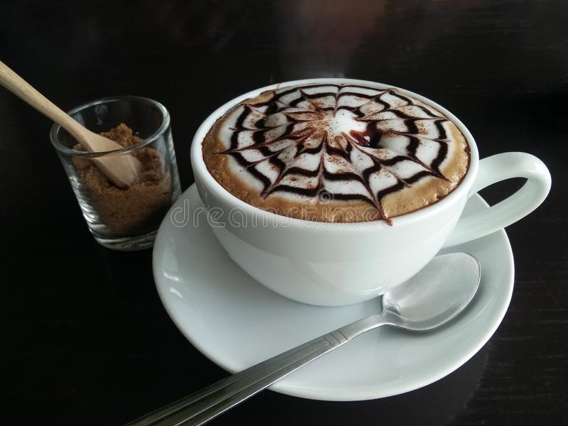 Close up of cappuccino or latte with frothy foam in white coffee cup on black wooden table in coffee cafe. Lifestyle coffee time royalty free stock images