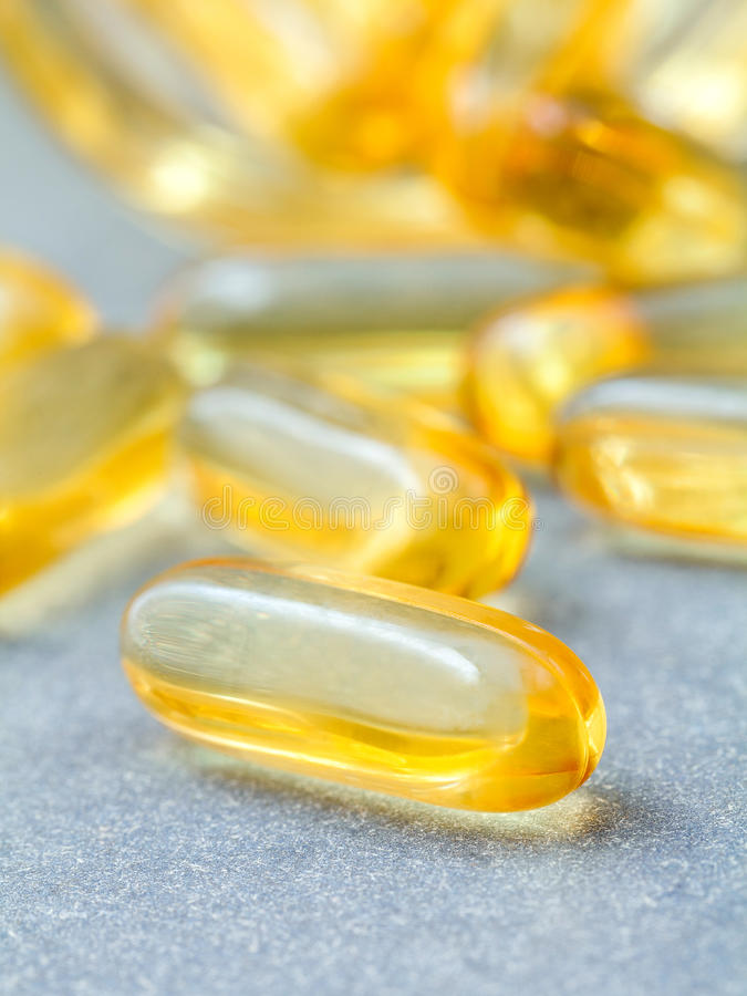 Close up capsules fish oil in Glass bottle .The supplement high. Vitamin E, omega 3, DHA and EPA.Selective focus depth of field stock photo