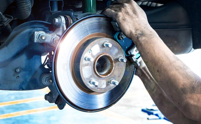 Close up car disk brake pad replacement service  with hand of mechanic man in car garage and copy space, use for disk brake royalty free stock photo