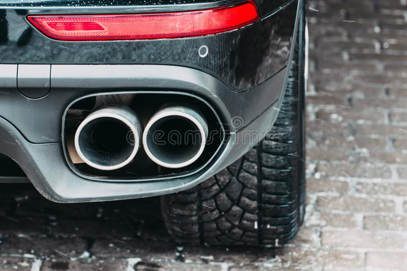 Close up of a car dual exhaust pipe parking lights, brake lights and wheel tires. Close up of a car dual exhaust pipe parking lights, brake lights and wheel royalty free stock images