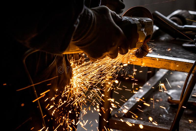 Close up of car mechanic hands welding grinding machine.Sparks of grinding machine while cutting car exhaust pipe stock image