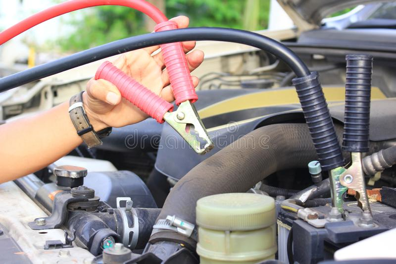Close-Up Car mechanic uses battery jumper cables to car battery royalty free stock photo