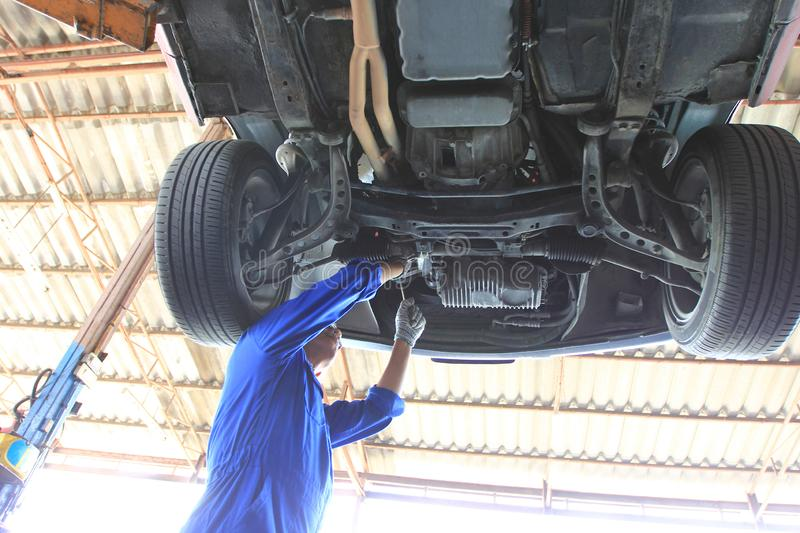 Close-up of car mechanic working under car in auto repair service royalty free stock images