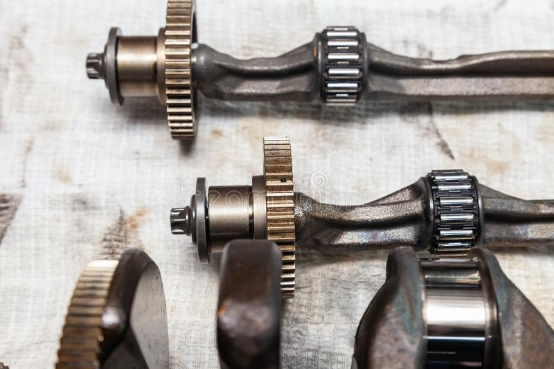 Close-up on a car shaft with gears and bearings removed for replacement on a workbench in a repair shop for vehicles. Auto service royalty free stock image