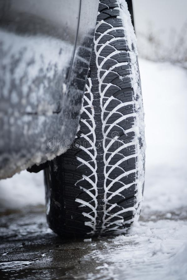 Car tire in winter on the road covered with snow, close up picture. Close up of car tire covered with snow on a slippery road, winter, icy, cold, vehicle royalty free stock images