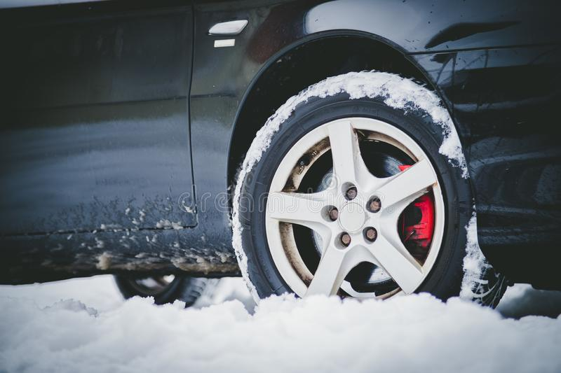 Car tire in winter on the road covered with snow, close up picture. Close up of car tire covered with snow on a slippery road, winter, icy, cold, vehicle stock photo