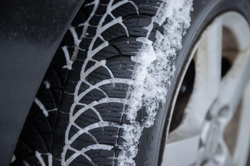 Car tire in winter on the road covered with snow, close up picture. Close up of car tire covered with snow on a slippery road, winter, icy, cold, vehicle stock images