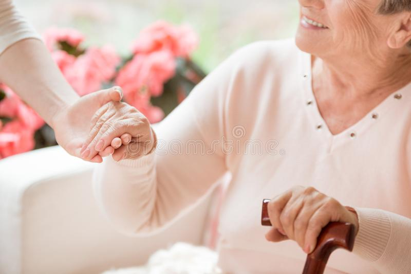 Close-up of caregiver supporting smiling senior woman with walki stock image