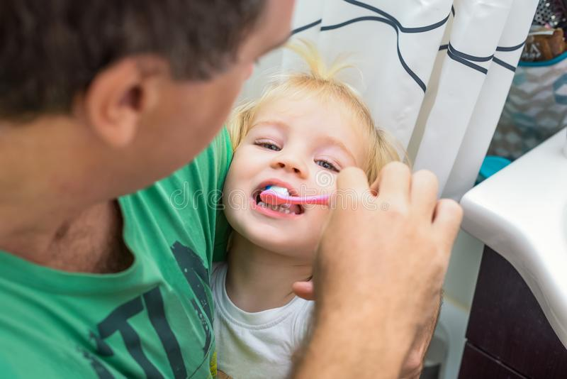 Close up caring father gently carefully brushing his little toddler daughter`s teeth in the bathroom. Family health care concept. royalty free stock photo