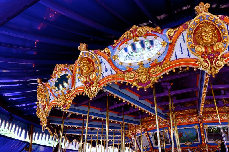 Merry-go-round Carousel in Bright Colors. Close up on carousel. Bright colors reflect off the mirrors. Camera angled for upward view of merry-go-round ornate stock photography