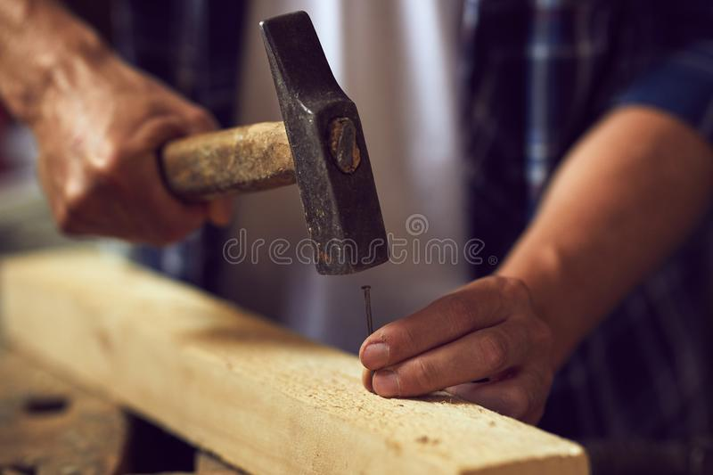 Close up carpenter hammering a nail into wooden plank royalty free stock photo