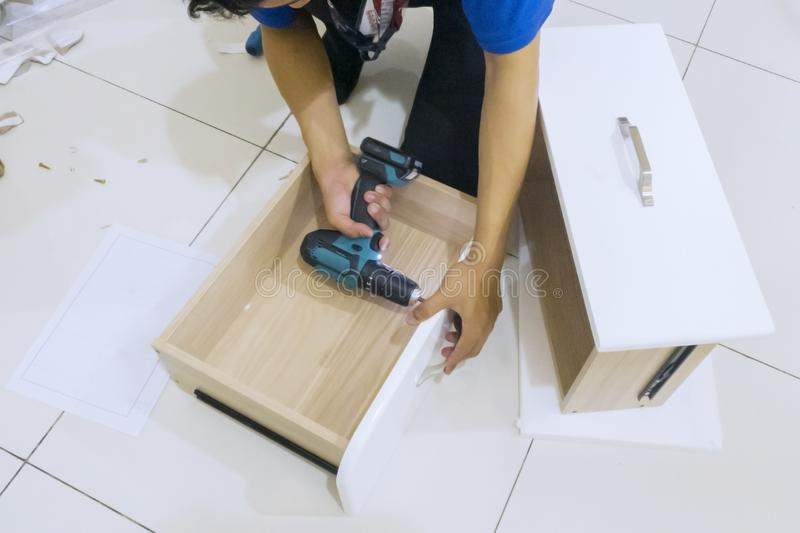 Carpenter hands installing a drawer with a drill stock photos