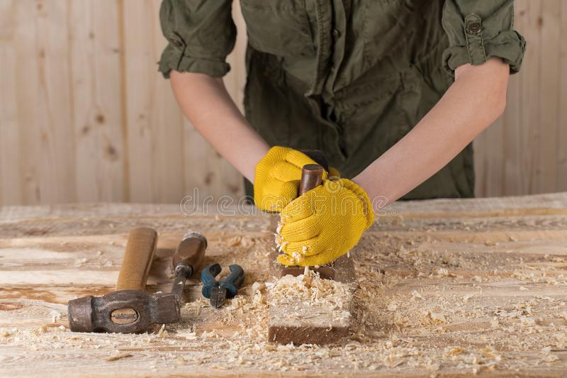Close up of a carpenter planing a plank of wood with a hand plane. Carpenter sucks a wooden board stock photos