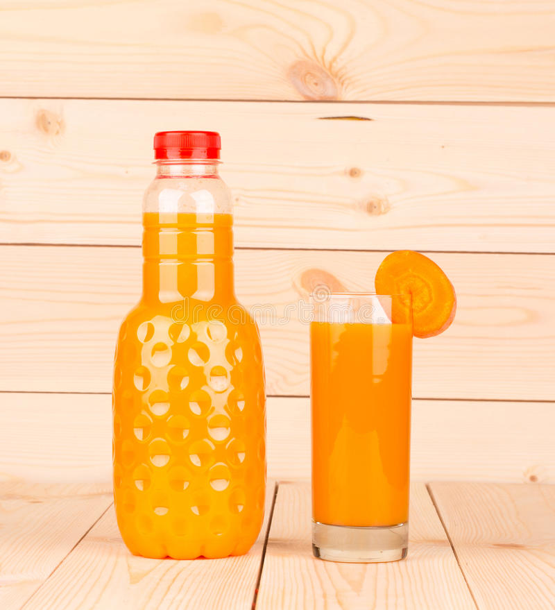 Close up of carrot juice in glass and bottle. royalty free stock images