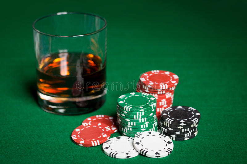 Close up of casino chips and whisky glass on table royalty free stock image