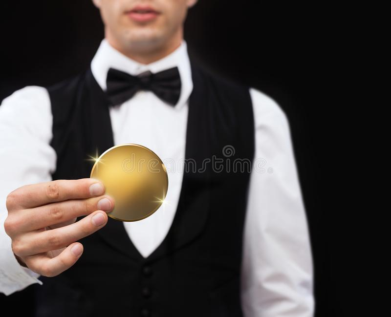 Close up of casino dealer holding golden coin stock photo