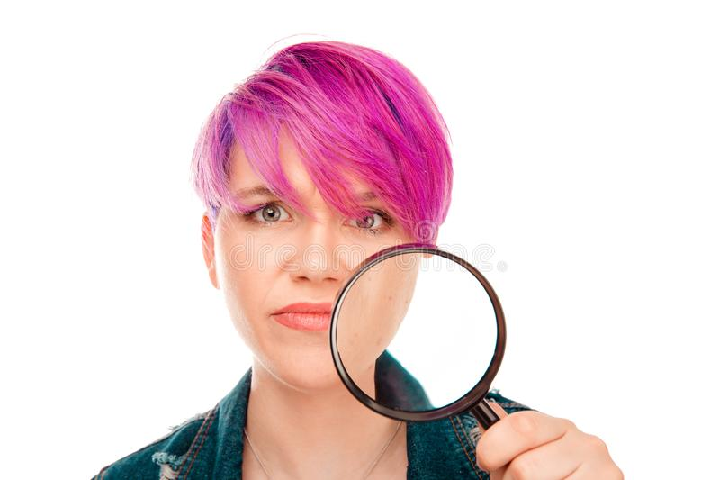 Girl looking at camera showing her acne with magnifier. Close-up of casual girl with pink hairstyle holding magnifying glass and looking at camera with emotion stock images