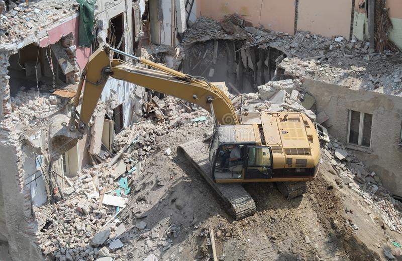 Close up of caterpillar excavator demolishing building.  stock photography