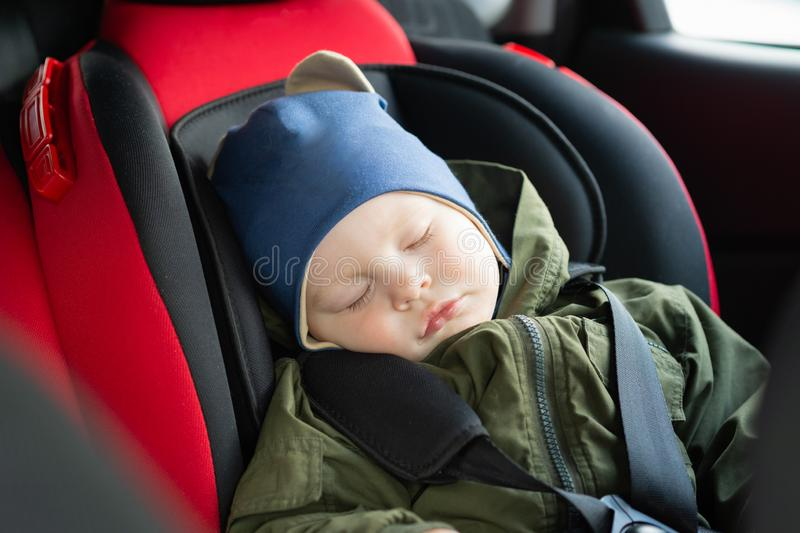 Close Up caucasian cute baby boy sleeping in modern car seat. Child traveling safety on the road. Safe way to travel. Fastened seat belts in a vehicle with royalty free stock image