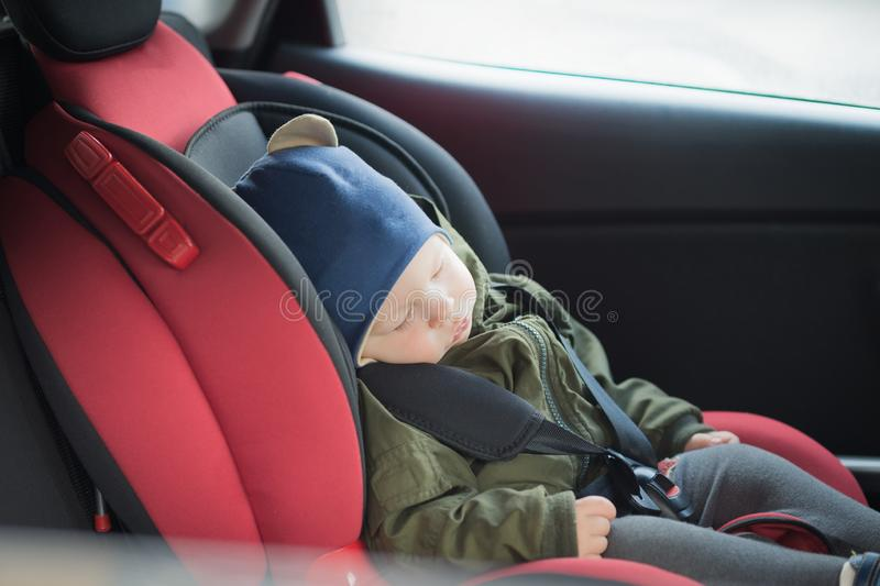 Close Up caucasian cute baby boy sleeping in modern car seat. Child traveling safety on the road. Safe way to travel. Fastened seat belts in a vehicle with stock image