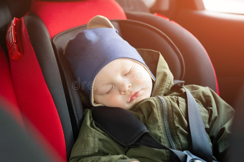 Close Up caucasian cute baby boy sleeping in modern car seat. Child traveling safety on the road. Safe way to travel. Fastened seat belts in a vehicle with stock photos