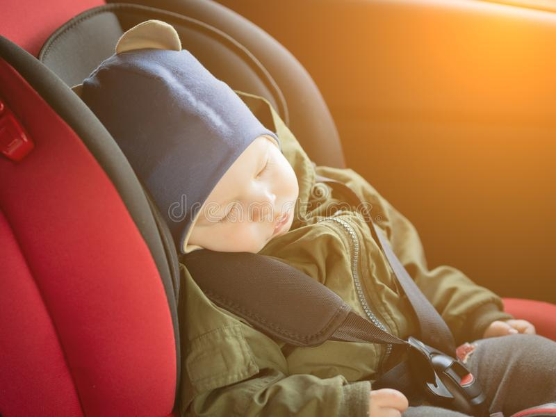 Close Up caucasian cute baby boy sleeping in modern car seat. Child traveling safety on the road. Safe way to travel. Fastened seat belts in a vehicle with royalty free stock images