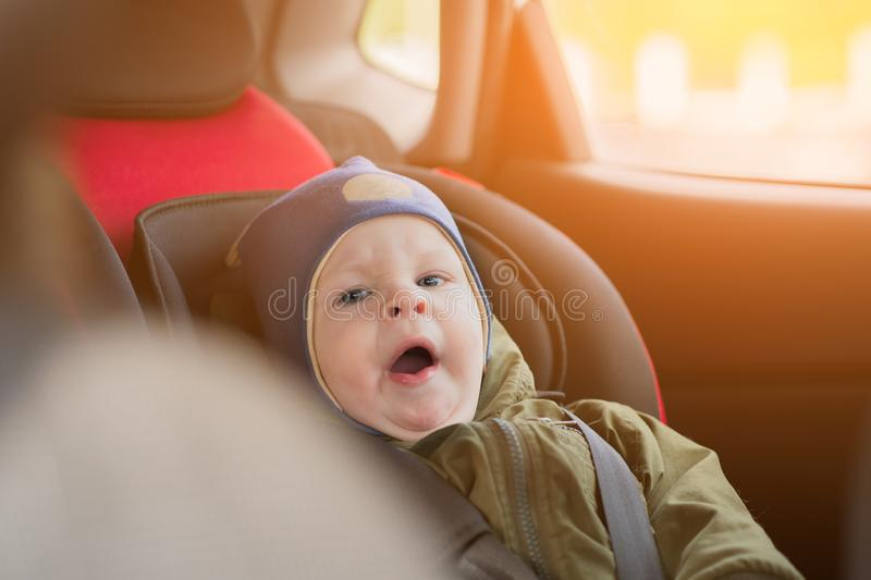 Close Up caucasian cute baby boy woke up and yawns in modern car seat. Child traveling safety on the road. Safe way to. Travel fastened seat belts in a vehicle stock image