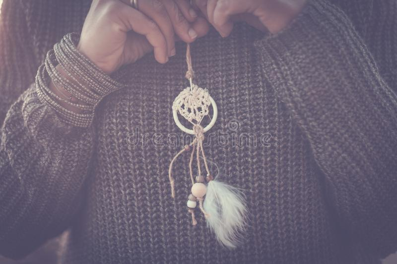 Close up of caucasian lady holding a little dream catcher on his chest wearing a grey warm sweater - autumn and protection concept royalty free stock photos