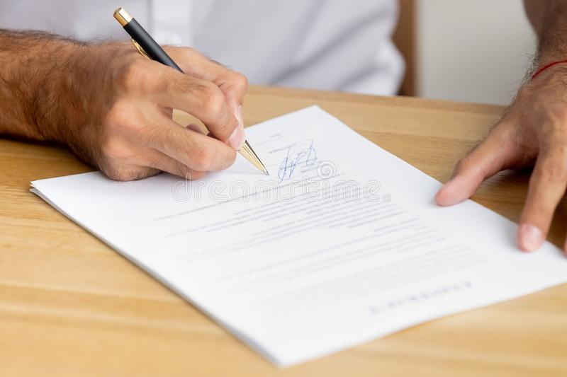 Close up caucasian male hands holding pen singing business paper. Contract sitting at desk. Confirmation and accepting collaboration or hiring employment royalty free stock images