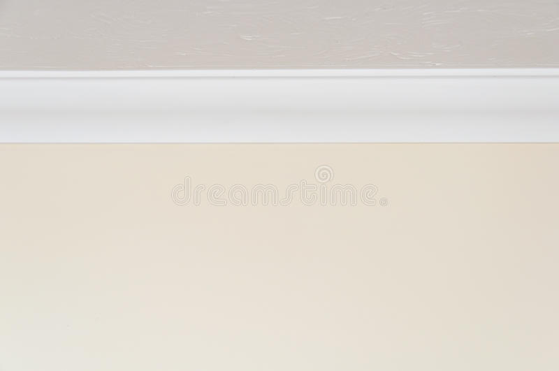 Close up of ceiling moulding. Close up of white ceiling moulding and light brown wall for background with copy space at top and bottom stock image