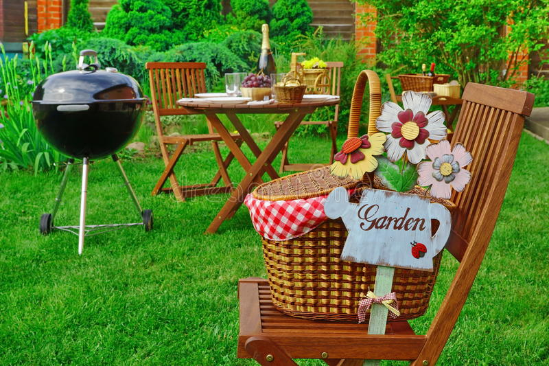 Close-up Of Chair With Hamper And Sign Garden, Party Scene. Close-up Of Chair With Hamper And Sign Garden, Family Home Party Scene, Outdoor Wooden Table With royalty free stock photos